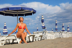 Woman in bathing suit sitting on white lounge. Beautiful young woman in bathing suit sitting on white chaise lounge and sunbathe, rows of white loungers and blue Royalty Free Stock Images