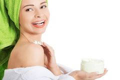 Woman in bathrobe applying cream on shoulder Stock Images