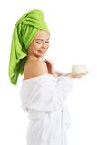 Woman in bathrobe applying cream on shoulder Stock Photography