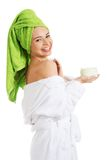 Woman in bathrobe applying cream on shoulder Royalty Free Stock Photo