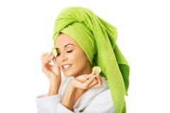 Woman in bathrobe applying cucumber on eyes Royalty Free Stock Photography