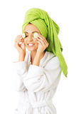 Woman in bathrobe applying cucumber on eyes Royalty Free Stock Images