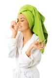 Woman in bathrobe applying cucumber on eyes Stock Image