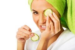 Woman in bathrobe applying cucumber on eyes Stock Images