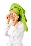 Woman in bathrobe applying cucumber on eyes Royalty Free Stock Images