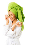 Woman in bathrobe applying cucumber on eyes Stock Images