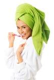 Woman in bathrobe brushing teeth Royalty Free Stock Photos