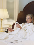Woman In Bathrobe With Cellphone And Wineglass In Bed Royalty Free Stock Photo