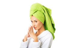 Woman in bathrobe clenching hands Stock Photo