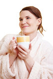 Woman in bathrobe with cup Stock Images
