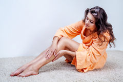 Woman in bathrobe doing legs waxing Royalty Free Stock Photography