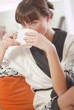 Woman in bathrobe drinking tea Stock Images