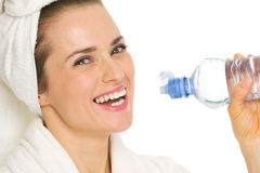 Woman in bathrobe drinking water from bottle Stock Images