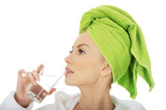 Woman in bathrobe drinks water. Royalty Free Stock Photos
