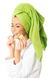 Woman in bathrobe eating cucumber Royalty Free Stock Images