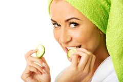 Woman in bathrobe eating cucumber Royalty Free Stock Photo