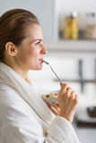 Woman in bathrobe enjoying breakfast in morning Royalty Free Stock Photos