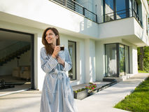 Woman in a bathrobe enjoying morning coffee. Young beautiful woman in a bathrobe enjoying morning coffee in front of her luxury home villa Stock Photography