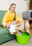Woman in bathrobe with feet in basin Stock Image