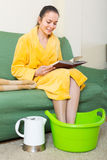 Woman in bathrobe with feet in basin. Positive young woman in bathrobe sitting with feet in basin Stock Image