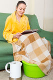 Woman in bathrobe with feet in basin. Smiling young woman in bathrobe sitting with feet in basin Stock Photo