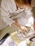 Woman in bathrobe handling finances Royalty Free Stock Photos