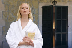 Woman in bathrobe holding books with eyes closed on patio royalty free stock image
