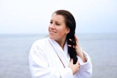 Woman in a Bathrobe Holding Her Hair Stock Photos