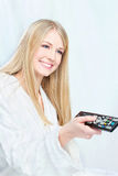 Woman in bathrobe holding remote controller Royalty Free Stock Photos