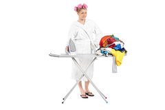 Woman in bathrobe ironing a pile of clothes Stock Images