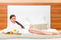 Woman in bathrobe is located on the bed Stock Image