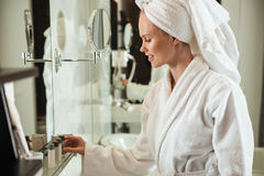 Woman in bathrobe looking at cosmetics near mirror. Young blonde woman in bathrobe and with towel on head looking at cosmetics near mirror Royalty Free Stock Images