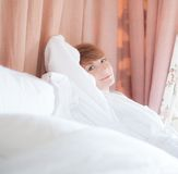 Woman in bathrobe lying on a  bed Royalty Free Stock Photos