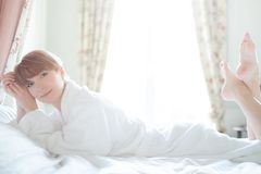 Woman in bathrobe lying on a bed Stock Photo