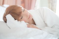 Woman in bathrobe lying on a bed Stock Image