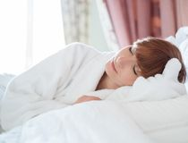 Woman in bathrobe lying on a bed Royalty Free Stock Images