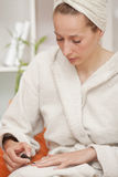Woman in bathrobe painting nails Stock Images