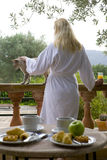 Woman in bathrobe petting cat on patio with breakfast in foreground Stock Image