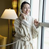 Woman in bathrobe on phone. Stock Photos