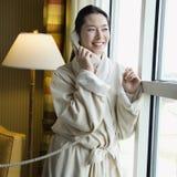 Woman in bathrobe on phone. stock photos