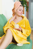 Woman in bathrobe putting cosmetic. Positive woman in bathrobe putting cosmetic treatment on face Stock Images