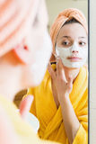 Woman in bathrobe putting cosmetic. Positive young woman in bathrobe putting cosmetic treatment on face Stock Images