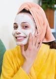 Woman in bathrobe putting cosmetic Stock Image
