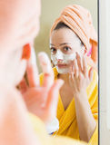 Woman in bathrobe putting cosmetic. Young woman in bathrobe putting cosmetic treatment on face Stock Photos