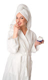 Woman in bathrobe is putting the cream Royalty Free Stock Photo