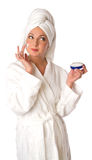 Woman in bathrobe is putting the cream Stock Photo