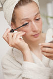 Woman in bathrobe putting mascara Stock Image