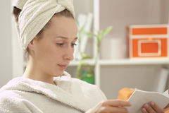 Woman in bathrobe reading book Stock Photo