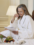 Woman In Bathrobe Reading Documents In Bed Stock Photos