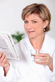 Woman in bathrobe reading newspaper Royalty Free Stock Image